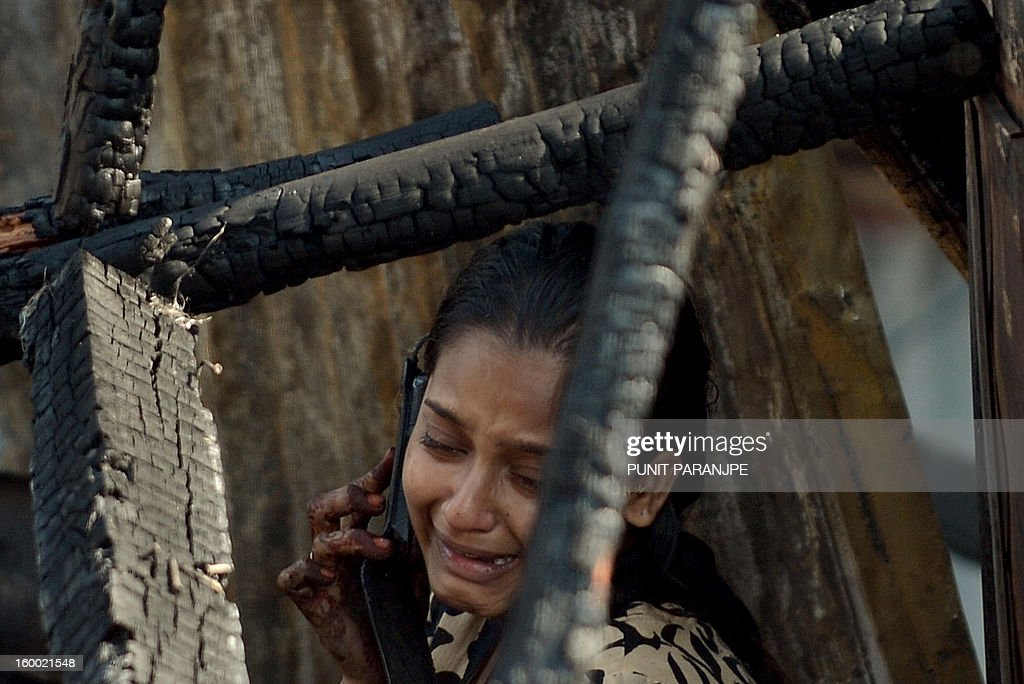 An Indian woman cries as she talks on the phone after a fire raged through the Nayanagar slum in Mumbai on January 25, 2013. A fire killed six people when it ripped through a slum in the heart of Mumbai on January 25 and left hundreds homeless, emergency services said. AFP PHOTO/ PUNIT PARANJPE