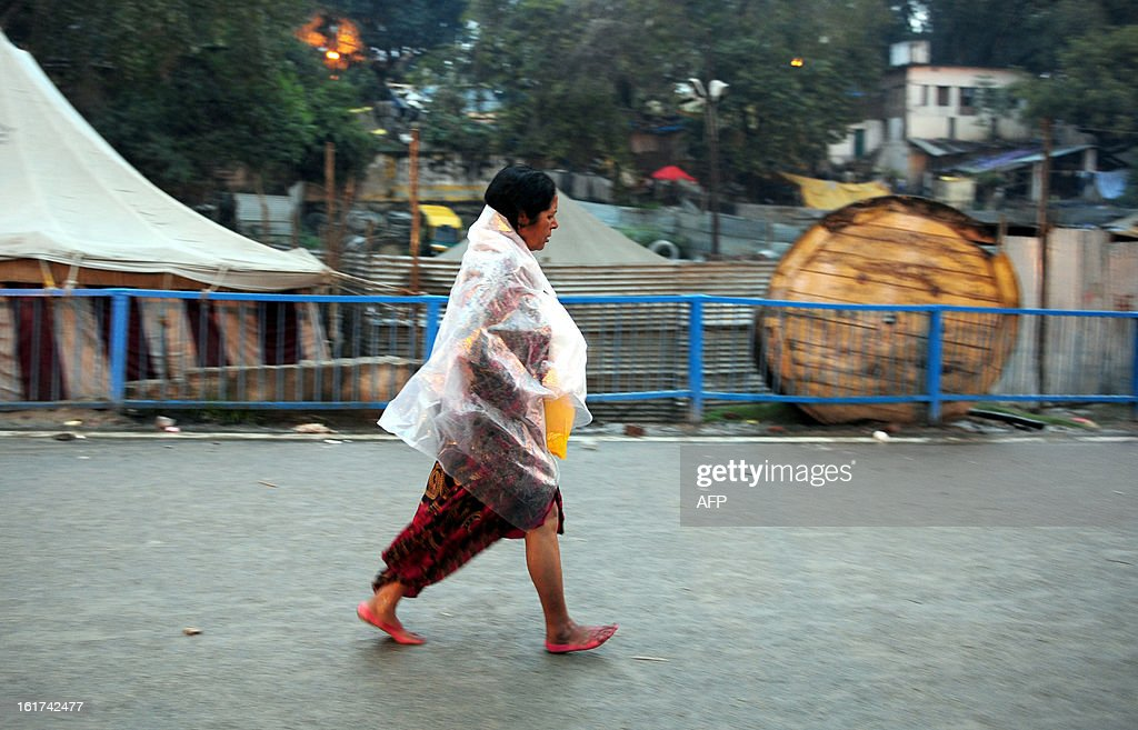 An Indian woman devotee covers herself with a plastic sheet during a rain shower in Allahabad on February 15, 2013. The Kumbh Mela in the town of Allahabad will see up to 100 million worshippers gather over 55 days to take a ritual bath in the holy waters, believed to cleanse sins and bestow blessings.
