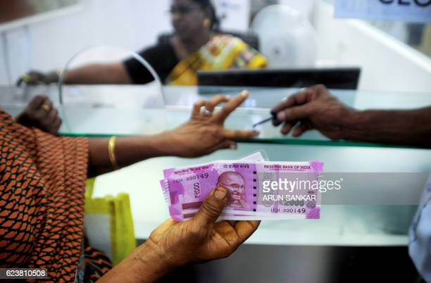TOPSHOT An Indian woman displays her 2000 rupee notes as she has her finger inked with indelible ink after exchanging withdrawn 500 and 1000 rupee...