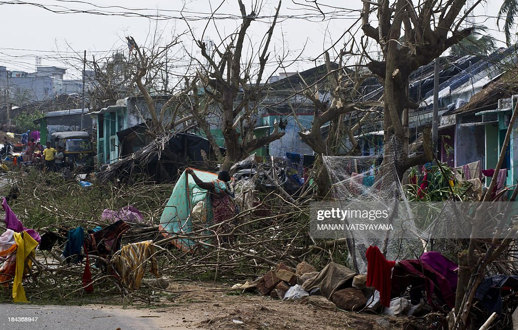 An Indian woman dries her sari amid debris at the fishermen's colony in Gopalpur on October 13, 2013. Cyclone Phailin left a trail of destruction along India's east coast and up to seven people dead after the biggest evacuation in the country's history helped minimise casualties.