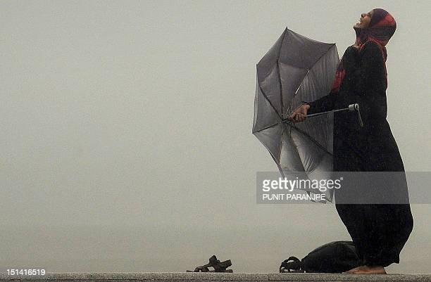 An Indian woman enjoys heavy rain showers at the sea front in Mumbai on September 3 2012 The monsoon rains a key to India's economy covered the...