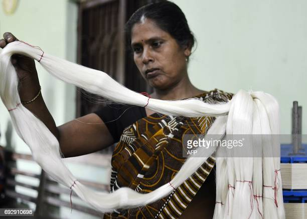 An Indian woman examines silk yarns at a silk factory in Dharmanagar in India's northeastern state of Tripura on June 6 2017 The silkworms are grown...