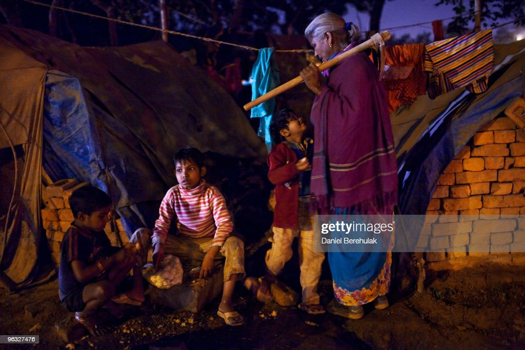 An Indian woman greets her children as she arrives to her temporary tent dwelling after a day of labouring on a construction project in front of the Jawaharlal Nehru Stadium on February 01, 2010 in New Delhi, India. The children accompany their parents to the work site, where if they are prepared to work, they will receive money for bread an milk and be provided with dinner by the contractor. The Commonwealth Games are due to be held in the Indian capital from October 3-14, 2010, but concerns remain over construction of its sporting and transport infrastructure. The sheer scale of the project has drawn an enormous population of migrant workers from all over India. This week the High Court of Delhi has sought a response from the Government over the alleged failure to provide all the benefits of labour laws to workers involved in construction work for the coming Commonwealth Games. Workers are being paid below the minimum wage in order to complete these projects whilst also being forced to live and work under sub standard conditions.
