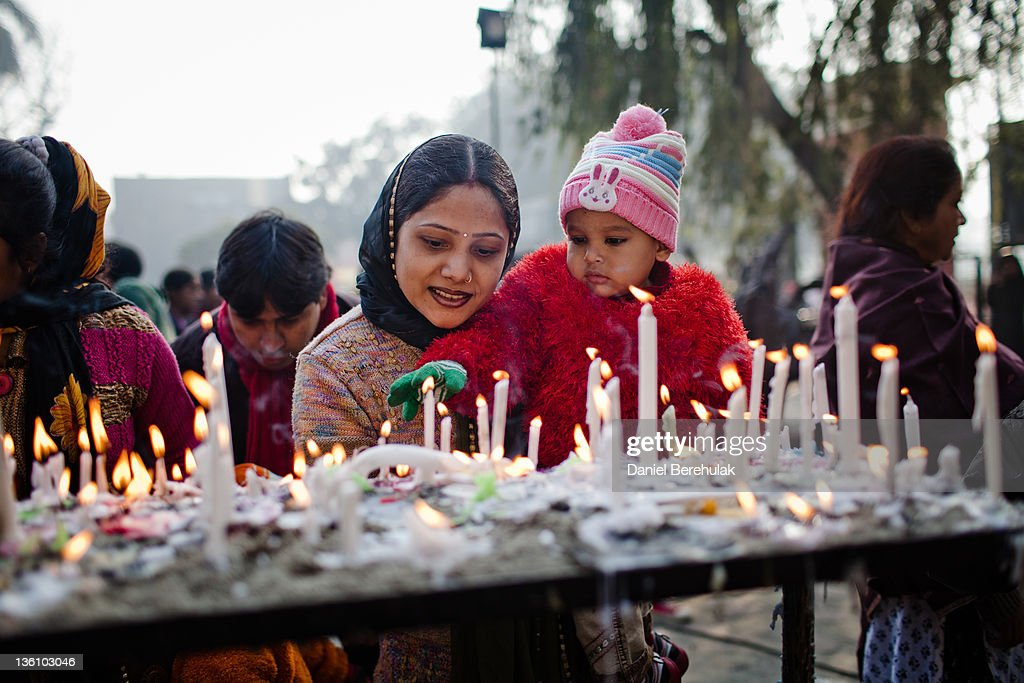 An indian woman helps a child to light a candle as christians gather