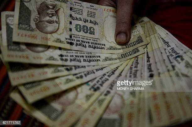 An Indian woman holds 500 INR currency notes at her home in Faridabad a suburb of New Delhi on November 8 2016 Indian Prime Minister Narendra Modi...