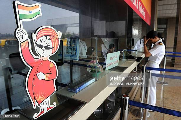 An Indian woman holds her head as she waits to reschedule her flight at the ticket window of India's flagship Air India at the domestic airport in...