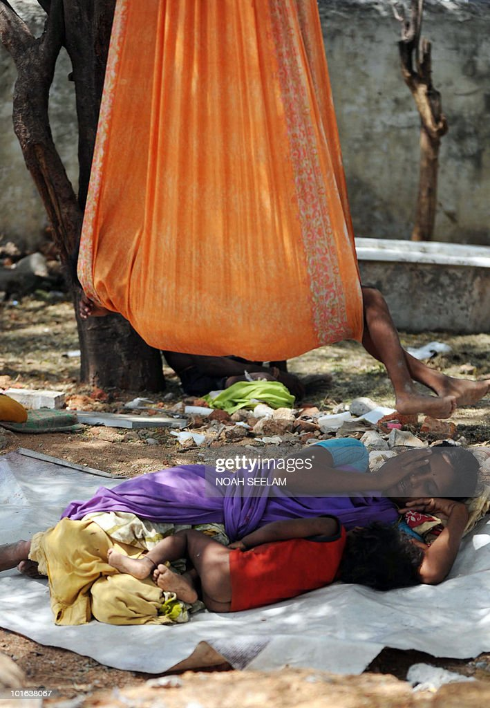 An Indian woman labourer and child sleep during a work break under the shade of a tree by the roadside in Hyderabad on June 5, 2010. AFP PHOTO/Noah SEELAM