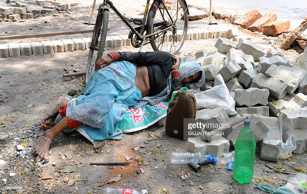 An Indian woman labourer takes a nap on the roadside in the heat of New Delhi on June 5, 2013. The weather department has forecast India will receive normal rains this year, raising prospects of a stronger performance by Asia's third-largest economy.