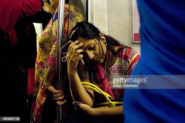 An Indian woman listens to her smartphone as she travels in the metro carriage reserved for women in New Delhi on July 14 2015 With the first stretch...