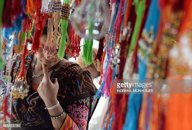 An Indian woman looks at 'rakhis' at a roadside shop ahead of the Hindu festival Raksha Bandhan in Mumbai on August 27 2015 The annual festival of...