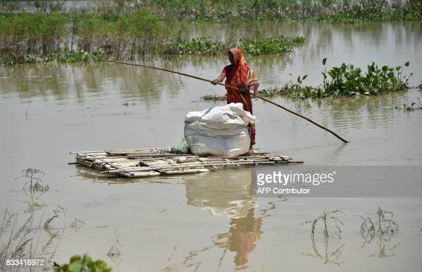 An Indian woman paddles a raft through floodwaters in Morigoan district in Indias northeastern state of Assam on August 17 2017 At least 221 people...