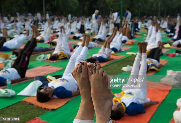 TOPSHOT An Indian woman points her toes upwards in a morning yoga session held to mark International Yoga Day in Lodhi Gardens in New Delhi on June...