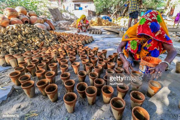 An Indian woman potter makes earthen lamps and other items ahead of Diwali festival in JaipurRajasthan India 08 Oct2017 People buy earthen lamps to...