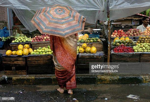 An Indian woman purchases fruits from a street vendor on a rain soaked street at Santacruz in Mumbai 01 August 2005 Monsoon rains lashed Mumbai again...