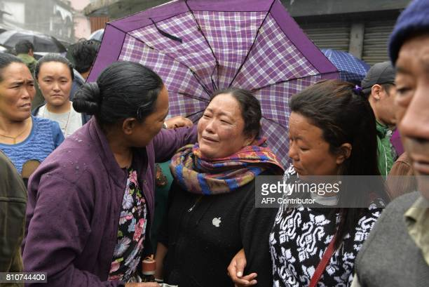 An Indian woman reacta as Gorkhaland supporters transport atop a vehicle the dead body of Tashi Bhutia who is claimed to be killed by police firing...