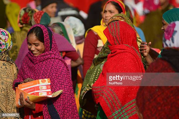 An indian woman returns after taking free gas connection card and a lunch packet given by Minister of state for Patrolium and natural gas Mr...