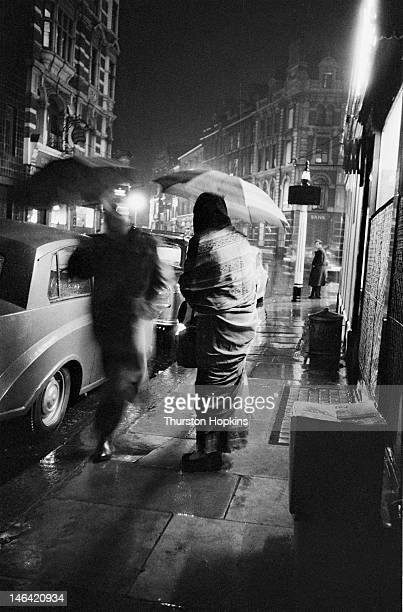 An Indian woman shelters under an umbrella on a rainy night in London October 1955 Original publication Picture Post 8572 Indians In London unpub
