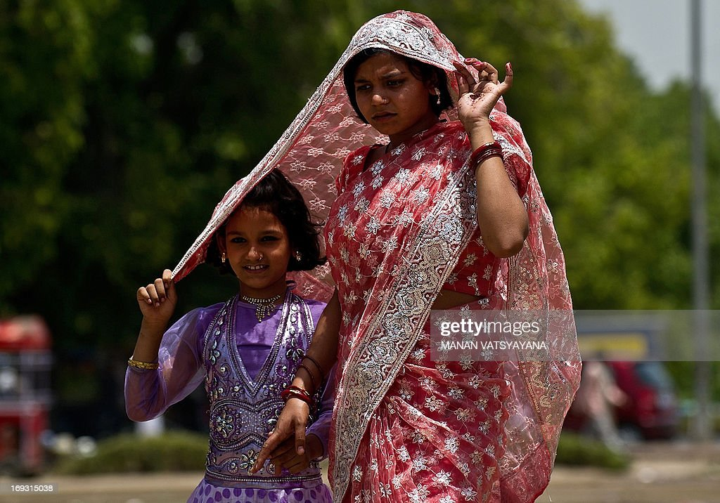 An Indian woman shields a child's head with her sari to provide shade from the sun in New Delhi on May 23, 2013. Heatwave conditions continued in the Indian capital, with temperatures registering a record high for the month of May at 45.6 degrees celsius. AFP PHOTO/MANAN VATSYAYANA