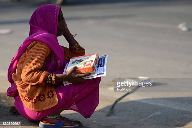 An indian woman sit on the fringes of a road taking free gas connection card and a lunch packet given by Minister of state for Patrolium and natural...
