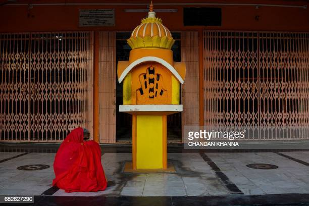 An Indian woman sits in the courtyard of a temple in Kekri some 78 kms south of Ajmer on May 13 in the northern state of Rajasthan / AFP PHOTO /...