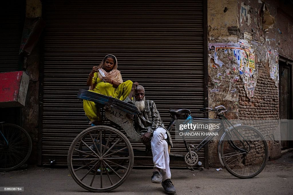 An Indian woman sits on a cycle rickshaw as the rickshaw puller waits for customers in the old quarters of New Delhi on May 31, 2016. / AFP / CHANDAN
