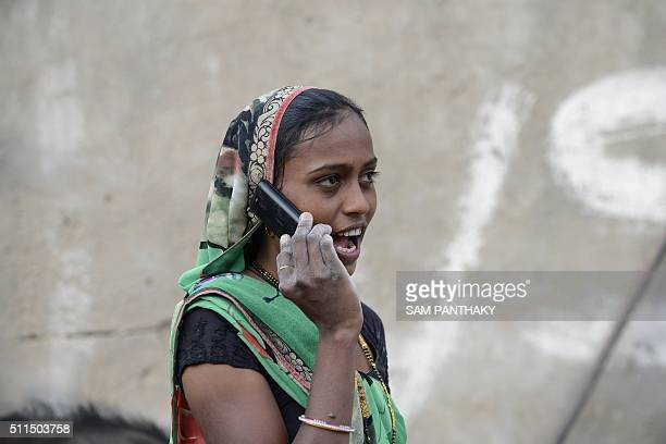 An Indian woman speaks on a mobile phone in Suraj village in Mehsana district some 100 km from Ahmedabad on February 20 2016 A village in Indian...