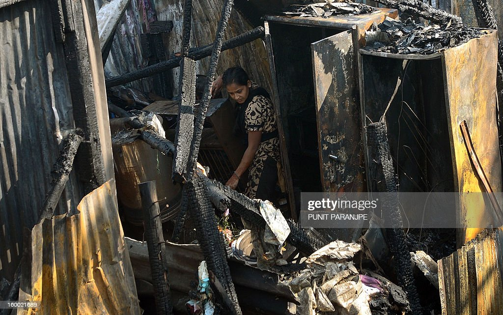 An Indian woman stands in her burnt-out house after a fire raged through the Nayanagar slum in Mumbai on January 25, 2013. A fire killed six people when it ripped through a slum in the heart of Mumbai on January 25 and left hundreds homeless, emergency services said.