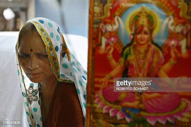 An Indian woman stands next to an image of Lakshmi the Hindu Goddess of wealth prosperity and fortune in the entrance to the Fair Price Shop a...