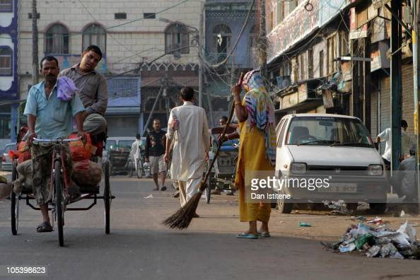 An Indian woman sweeps a street in Old Delhi as a rickshaw driver transports a passenger on October 14 2010 in Delhi India An investigation into...