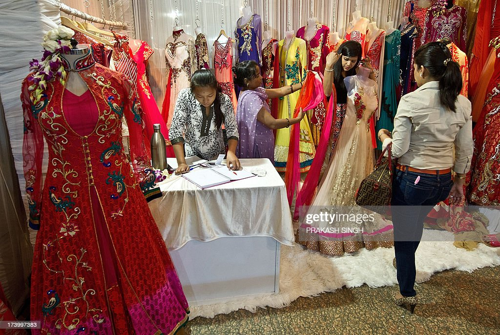 An Indian woman tries on a dress during the 'Wedding Asia' exhibition in New Delhi on July 19, 2013. The Excelsior group have organised the exhibition at The Ashok Hotel in the Indian capital from July 19-21. AFP PHOTO/ Prakash SINGH