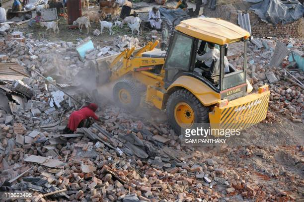 An Indian woman tries to retrieve her belongings from under the debris of her demolished house after bulldozers demolished homes in Dudheshwar area...