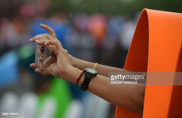 An Indian woman use a yoga mat to protect herself from rain as she takes a photograph with her phone during the 3rd International Yoga Day at...