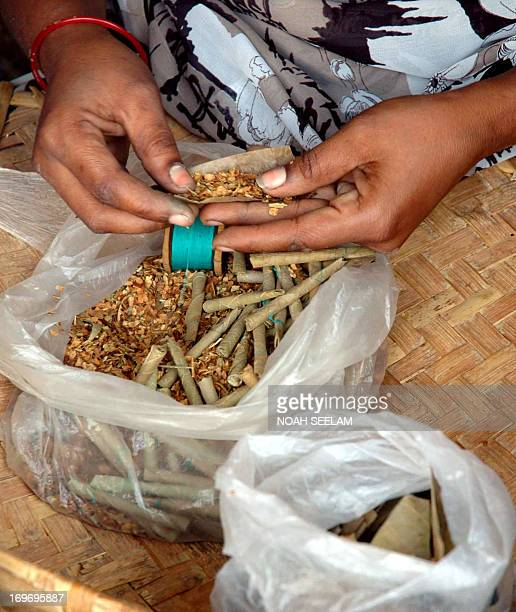 An Indian woman uses a combination of chewing tobacco and tendu leaves to make 'beedis' in Karimnagar some 160kms north of Hyderabad 30 May 2007...