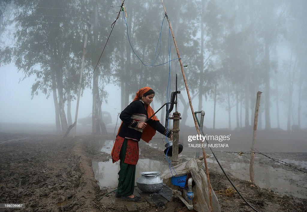 An Indian woman uses a handpump to during a dense fog along the India-Pakistan border in Suchit-Garh, 36 kms southwest of Jammu on January 10, 2013. The beheading of an Indian soldier may have sparked a war of words between Delhi and Islamabad but the two nuclear rivals are both determined to prevent it from wrecking a fragile peace process. Two Indian soldiers died after a firefight erupted in disputed Kashmir on Tuesday as a patrol moving in fog discovered Pakistani troops about 500 metres (yards) inside Indian territory, according to the Indian army. AFP PHOTO/Tauseef MUSTAFA