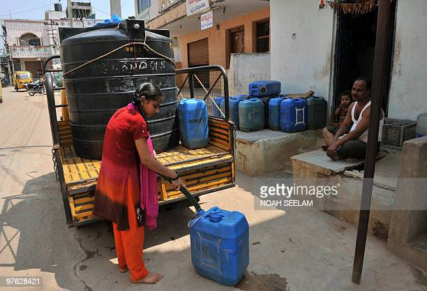 An Indian woman uses a hose to fill a jerrycan from a water tank on the rear of a pickup truck on the outskirts of Hyderabad on March 11 which is...