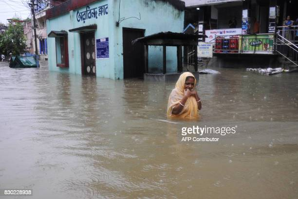 An Indian woman wades through a flooded street during a heavy downpour in Agartala the capital of northeastern state of Tripura on August 11 2017 /...
