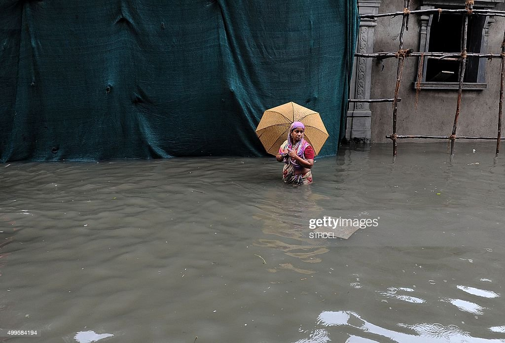 TOPSHOT An Indian woman wades through floodwaters in Chennai on December 2 2015 India has deployed troops to Tamil Nadu and closed the main airport...