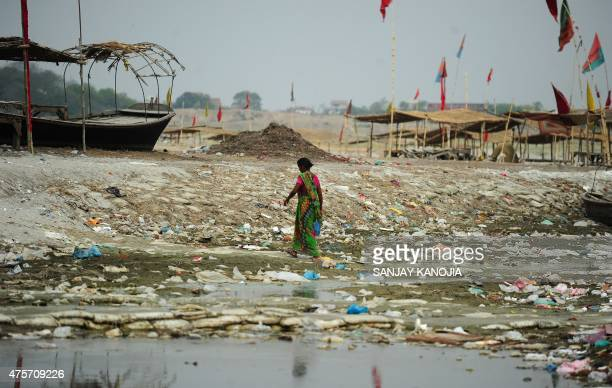 An Indian woman walks amogst plastic bags and garbage strewn on the banks of the River Ganges at Sangam the confluence of the Ganges Yamuna and...