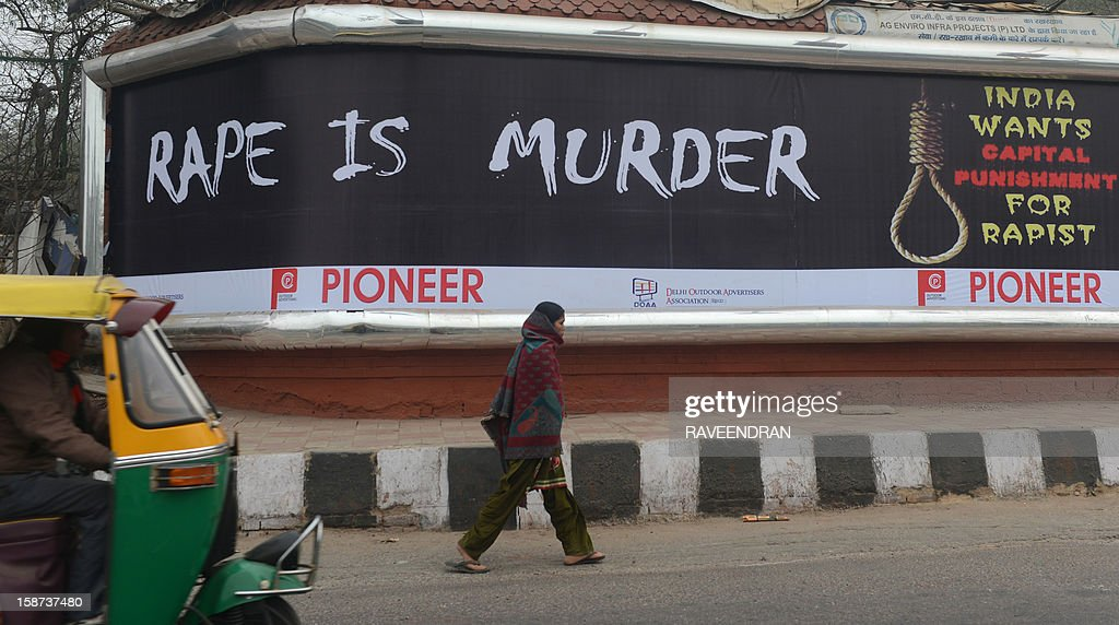 An Indian woman walks past a billboard, calling for capital punishment against rape, in New Delhi on December 27, 2012. An Indian student who was left fighting for her life after being brutally gang raped on a bus in New Delhi arrived December 27 in Singapore for treatment at a leading hospital. The attack sparked a wave of protests across India in which a policeman died and more than 100 police and protestors were injured.