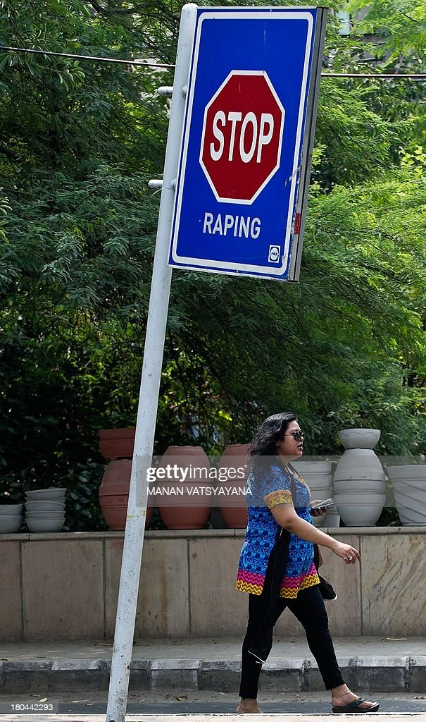 An Indian woman walks past a stop sign condemning rape outside the Saket Court Complex in New Delhi on September 13, 2013. Four men will learn if they are to hang for the shocking murder and gang rape of an Indian student after her parents begged for the 'cold-blooded' killers' execution.