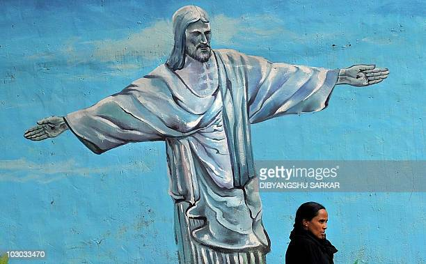 An Indian woman walks past a wall mural depicting Jesus Christ in Bangalore on July 22 2010 AFP PHOTO/Dibyangshu SARKAR