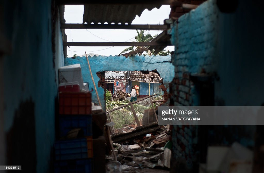 An Indian woman walks past debris at the fishermen's colony in Gopalpur on October 13, 2013. Cyclone Phailin left a trail of destruction along India's east coast and up to seven people dead after the biggest evacuation in the country's history helped minimise casualties.