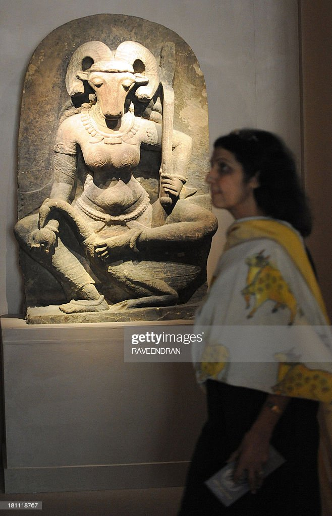 An Indian woman walks past the 10th century stone sculpture of the 400 kg, 4.5 foot high 'Yogini', inaugurated by Indian Minister for External Affairs, Salman Khurshid and Minister of Culture, Chandresh Kumari Katoch, at the National Museum in New Delhi on September 19, 2013. The 10th century sculpture of a female deity with a buffalo head was acquired by French art collector Robert Schrimpf from an unnamed source and donated by his widow, Martine Schrimpf to the Indian embassy in Paris in 2008. AFP PHOTO/RAVEENDRAN