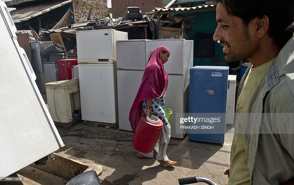 An Indian woman walks past used refrigerators on sale while carrying water buckets at a slum colony in New Delhi on May 23, 2013. Heatwave conditions continued in the Indian capital, with temperatures registering a record high for the month of May at 45.6 degrees celsius. AFP PHOTO/ Prakash SINGH