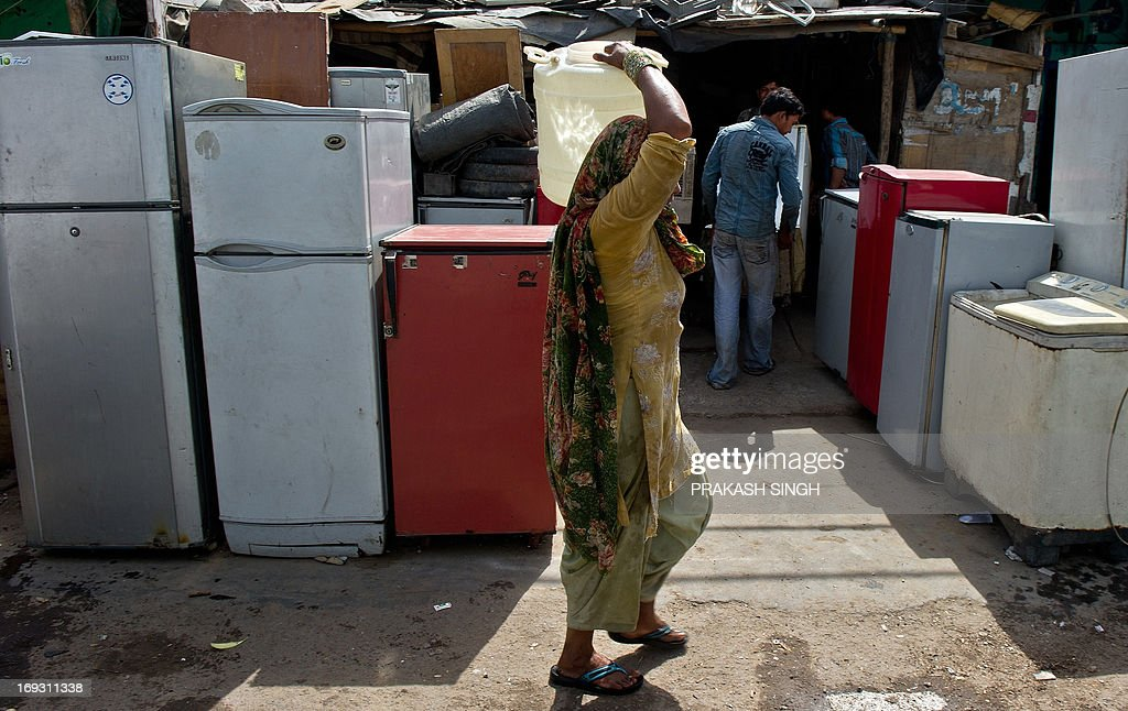 An Indian woman walks past used refrigerators on sale while carrying a water bucket at a slum colony in New Delhi on May 23, 2013. Heatwave conditions continued in the Indian capital, with temperatures registering a record high for the month of May at 45.6 degrees celsius. AFP PHOTO/ Prakash SINGH