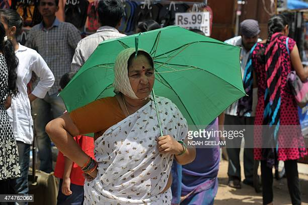 An Indian woman walks with an umbrella on a hot summer day in Hyderabad on May 26 2015 More than 430 people have died in two Indian states from a...