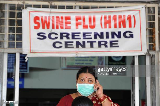 An Indian woman wearing a mask talks on her mobile phone outside the H1N1 swine flu screening centre at the Government Gandhi Hospital in Hyderabad...