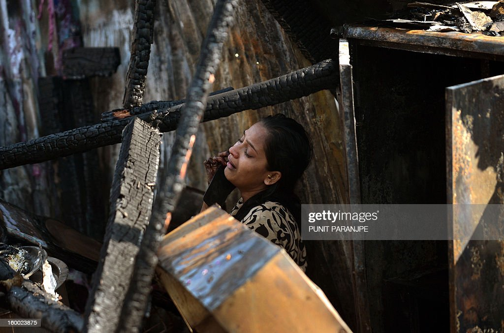 An Indian woman weeps as she speaks on the phone in her burnt-out house after a fire raged through the Nayanagar slum in Mumbai on January 25, 2013. A fire killed six people when it ripped through a slum in the heart of Mumbai on January 25 and left hundreds homeless, emergency services said.