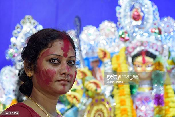 An Indian woman with vermilion powder in fer face