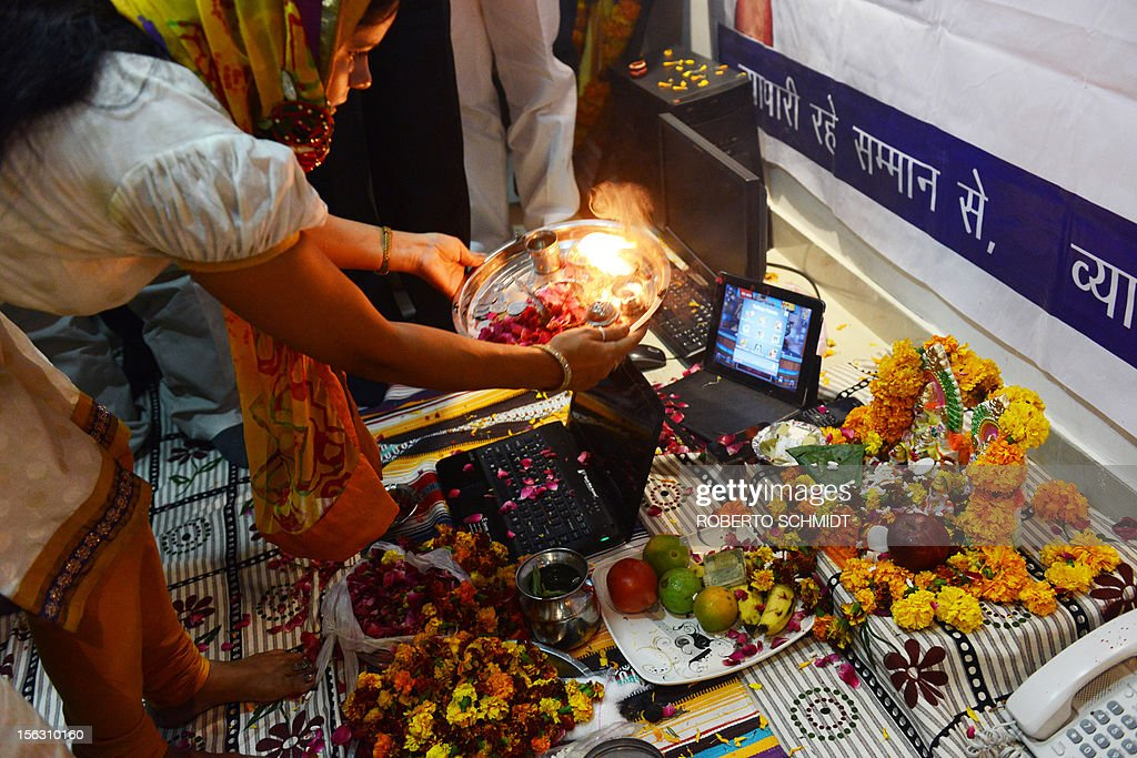 An Indian woman working for a local trading organization waves a flame over a laptop and an iPad as they worship electronic gadgets including iPads, laptops and mobile phones on Diwali, the Festival of Lights at their office in New Delhi on November 13, 2012. Since ages, the worshipping of account books has been an essential part of Diwali for the business community in India for prosperity of business. Signifying the modernisation of the retail trade in India, some traders are now including the worshipping of electronic gadgets. The festival of Diwali celebrates the victory of good over evil, light over darkness and knowledge over ignorance. AFP PHOTO/Roberto Schmidt